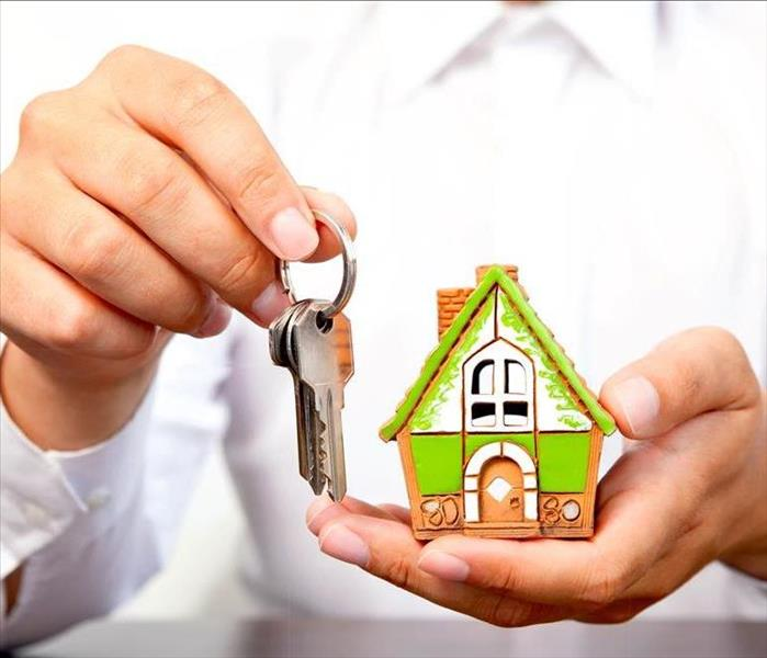 Employee holding miniature house and bundle of keys