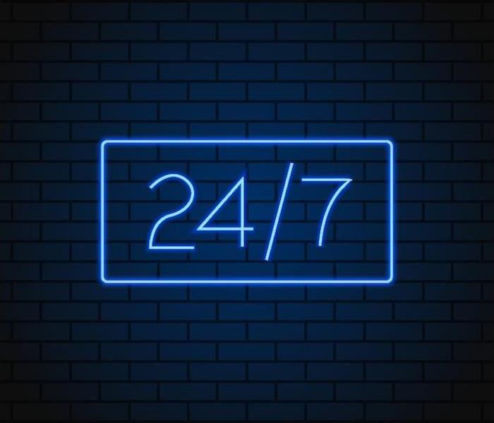 a large 24/7 blue neon sign hanging on brick wall