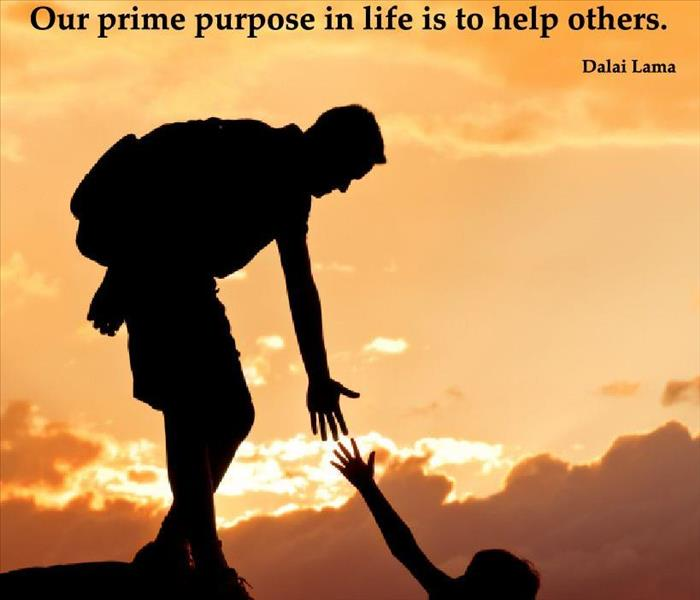 "picture of a person helping a person up a hill and a quote from the Dalia Lama ""our prime purpose in life is to help others"""